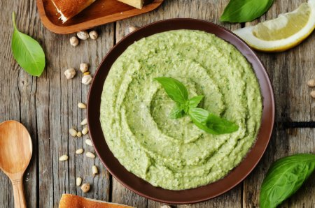 Photo for Basil pesto hummus on a dark wood background. the toning. selective focus - Royalty Free Image