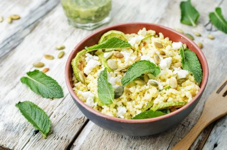Photo for Zucchini, millet, mint, pumpkin seeds, goat cheese salad with coriander dressing. the toning. selective focus - Royalty Free Image