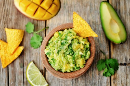 Photo for Mango guacamole with corn chips on a dark wood background. the toning. selective focus - Royalty Free Image