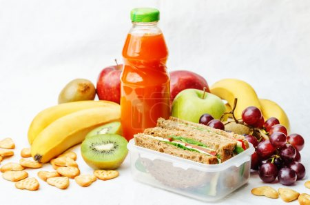 Photo for School lunch with a sandwich, fresh fruits, crackers and juice. the toning. selective focus - Royalty Free Image