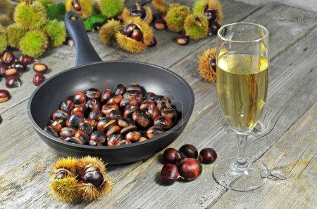Photo pour Photo de châtaignes grillées avec un verre de vigne blanc - image libre de droit