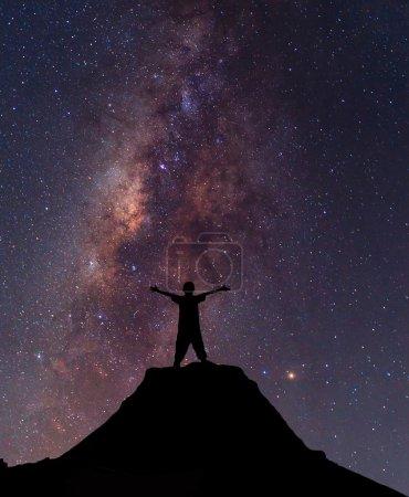Un garçon debout sur le sommet de la montagne au-dessus des nuages. Succès