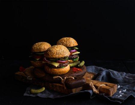 Foto de Hamburguesas de carne fresca con encurtidos y especias sobre fondo de tablas de madera rústica, negro. Enfoque selectivo, espacio de copia - Imagen libre de derechos