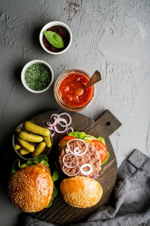 Photo for Fresh homemade burgers on dark serving board with spicy tomato sauce, green salt, pepper, pickles and onion over concrete textured background. Top view, copy space - Royalty Free Image