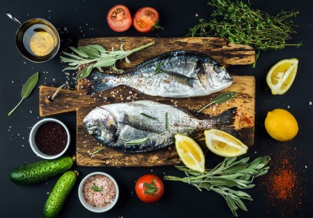Photo for Fresh uncooked dorado or sea bream fish with lemon, herbs, oil, vegetables and spices on rustic wooden board over black backdrop, top view - Royalty Free Image