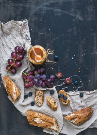 Photo for French baguette cut into pieces, red grapes, blueberry and salty caramel sauce on linen towel over rustic dark background with a copy space. Top view, vertical - Royalty Free Image