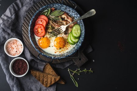 Photo for Breakfast set. Pan of fried eggs with bacon, fresh tomato, cucumber, sage and bread on dark serving board over black background, top view, copy space - Royalty Free Image