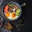 Breakfast set. Pan of fried eggs with bacon, fresh tomato, cucumber, sage and bread on dark serving board over black background, top view, copy space