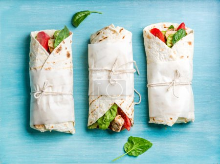 Photo for Healthy lunch snacks. Tortilla wraps with grilled chicken fillet and fresh vegetables on blue painted wooden background. Top view - Royalty Free Image