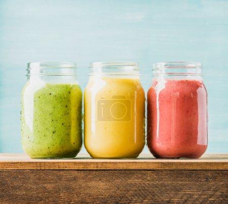 Photo pour Fraîchement mélangé les nectars de fruits de différentes couleurs et de saveurs en bocaux de verre. Jaune, rouge, vert. Fond bleu turquoise - image libre de droit