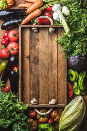 Photo for Fresh raw vegetable ingredients for healthy cooking or salad making with rustic wooden tray in center, top view, copy space. Diet or vegetarian food concept, vertical composition - Royalty Free Image