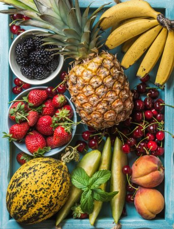 Photo pour Variété de fruits de l'été en bonne santé. Cerises, fraises, framboises, pêches, bananes, tranches de melon et menthe feuilles sur fond bleu. Vue de dessus - image libre de droit