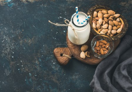 Fresh almond milk in bottle with almonds