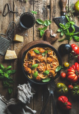 Photo for Italian pasta spaghetti with tomato sauce and meatballs in cast iron pan with Parmesan cheese, fresh basil, tomatoes and glass of wine over old rustic wooden background. Top view, vertical composition - Royalty Free Image