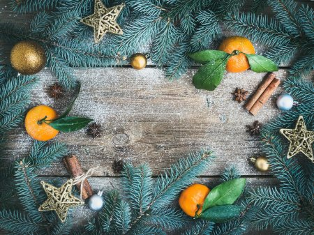 Photo pour Christmas (New Year) decorations: fur-tree branches, golden glass balls, golden glittering toy stars, fresh mandarins, cinnamon sticks and anise stars on a rough wooden background with a copy space - image libre de droit