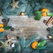 Christmas (New Year) decorations: fur-tree branches, golden glass balls, golden glittering toy stars, fresh mandarins, cinnamon sticks and anise stars on a rough wooden background with a copy space