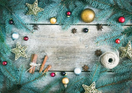 Christmas (New Year) decoration background: fur-tree branches, golden, red and silver glass balls, golden glittering toy stars, cinnamon sticks and anise stars on a rough wooden desk with a copy space