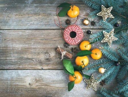Photo pour Décoration de Noël (Nouvel An) ensemble de fond : branches de sapin, boules de verre, étoiles dorées scintillantes jouet, bâtons de cannelle, étoiles d'anis et mandarines fraîches avec des feuilles vertes sur un bureau en bois rugueux avec un espace de copie. Vue du dessus - image libre de droit