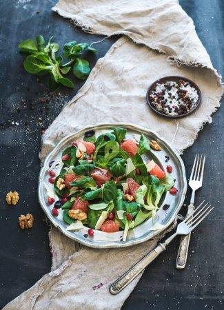Photo for Spring salad with lambs lettuce, grapefruit, garnet, walnuts in vintage metal plate over dark grunge backdrop - Royalty Free Image