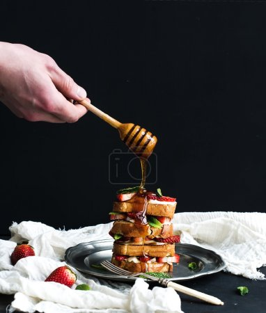 French toasts tower with strawberry, cream cheese and mint, hand is pouring honey over top of it