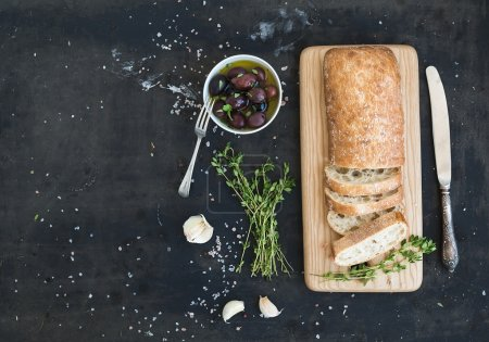 Photo for Italian ciabatta bread cut in slices on wooden chopping board with herbs, garlic and olives over dark grunge backdrop, copy space, top view - Royalty Free Image