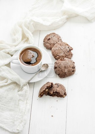 Chocolate cookies with almond and cranberries, cup of coffee, white wooden backdrop