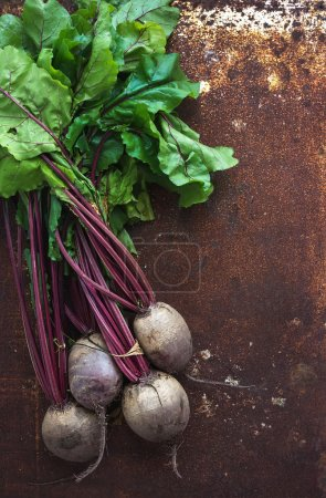 Photo for Bunch of fresh garden beetroots over grunge rusty metal backdrop, top view, copy space - Royalty Free Image