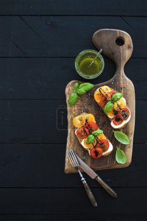 Photo for Tomato, mozzarella and basil sandwiches on dark wooden chopping board, pesto jar, dinnerware over black background, top view, copy space - Royalty Free Image