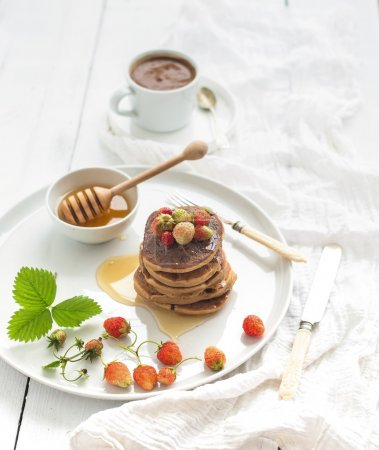 Photo for Breakfast set. Buckwheat pancakes with fresh garden strawberries, honey and cup of coffee over white wooden backdrop - Royalty Free Image