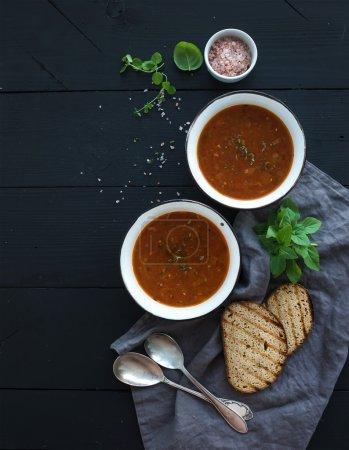 Photo pour Soupe de tomate rôtie avec basilic frais, épices et pain dans des bols en métal rustiques sur fond noir, vue du haut, espace de copie - image libre de droit