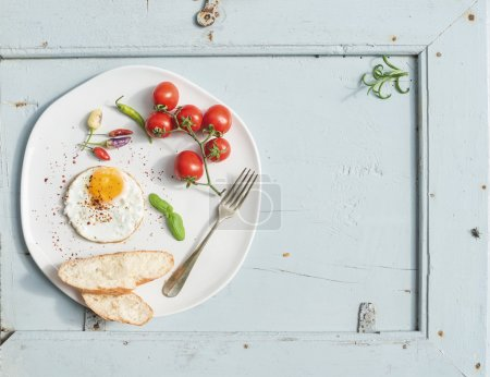 Photo for Breakfast set. Fried egg, bread slices, cherry tomatoes, hot peppers and herbs on white ceramic plate over light blue wooden backdrop, top view, copy space - Royalty Free Image