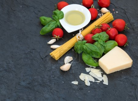 Photo for Ingredients for cooking pasta. Spaghetti, olive oil, garlic, Parmesan cheese, tomatoes and fresh basil on black slate background, top view, copy space - Royalty Free Image