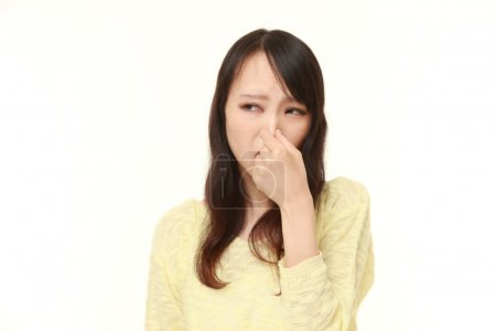 Japanese woman holding her nose because of a bad smell
