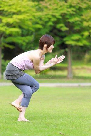 Japanese woman outside doing yoga eagle pose