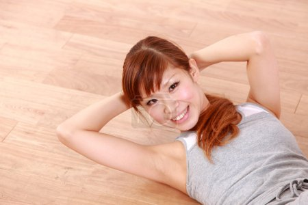 Young Japanese woman doing tight stomach crunches