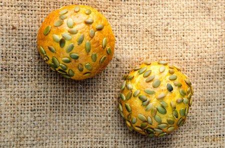 Several pumpkin buns with pumpkin seeds on burlap....