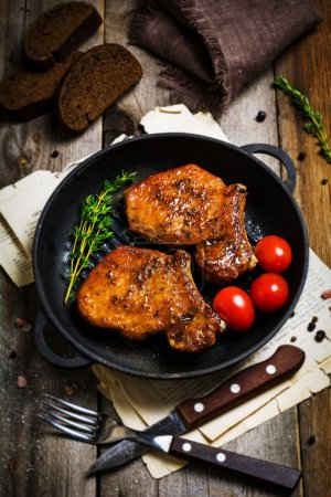 Grilled pork chops with thyme and cherry tomatoes in iron skillet