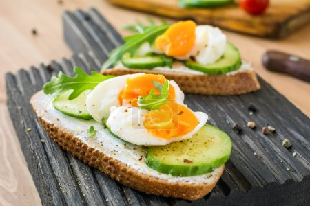 Photo for Tasty breakfast or snack toasts with cream cheese, fresh sliced cucumber and boiled egg, garnished with arugula leaves and spices on wooden cutting board. Selective focus - Royalty Free Image