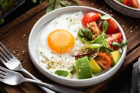 Photo pour Aliments sains pour le petit-déjeuner dans une assiette, œufs ensoleillés et salade d'avocats aux tomates avec germes et graines de chanvre - image libre de droit