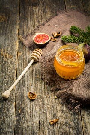 Photo pour Pot de miel, figues fraîches et noix sur table rustique en bois. Nourriture de Noël nature morte, foyer sélectif, lumière naturelle, image tonique chaude - image libre de droit