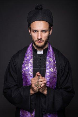 Photo pour Humble prêtre avec la Croix chrétienne. Portrait studio sur fond noir - image libre de droit