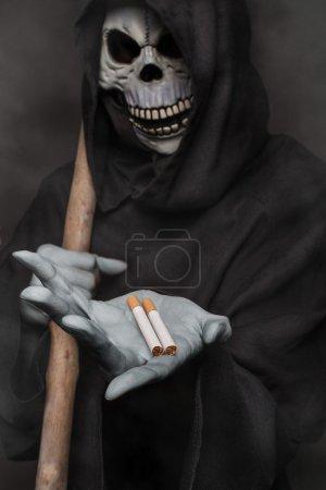 The concept: smoking kills. Grim reaper holding ci...