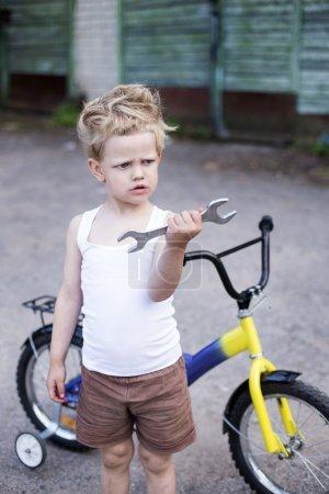 Funny toddler boy repairing his broken bike. Childhood.Cycling