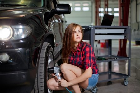 Photo for Female mechanic changing tire with air impact wrench. Young sexy woman in checked shirt - Royalty Free Image
