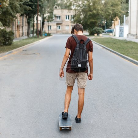 Young handsome guy with a backpack riding a skateboard on the road