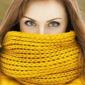 Hübsche Frau in einem gelben stricken Schal in die Kamera schaut. Beaut