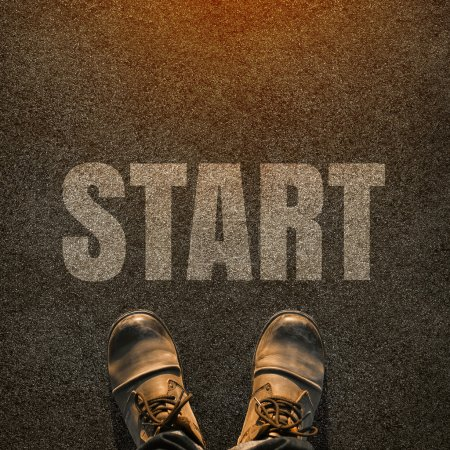 Photo for A pair of feet on a tarmac road with white print of the word start for the concept of starting point. Start concept background. - Royalty Free Image