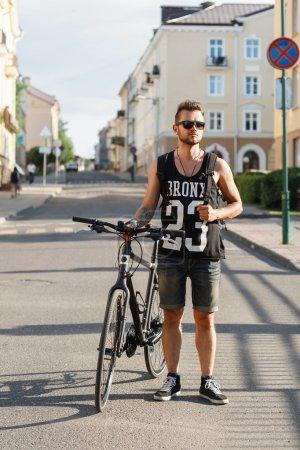 Photo pour Homme jeune hipster à vélo à pied dans la ville. T-shirt noir avec impression 23 - image libre de droit