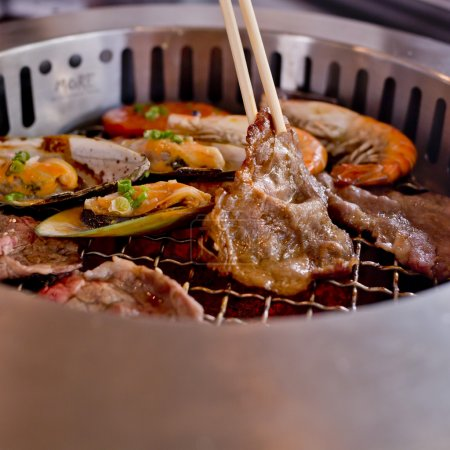 Mixed Roasted Meat and Seafood and Chopsticks on the BBQ Grill o
