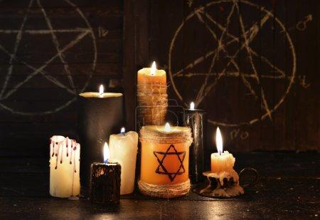 Warlock or evil burning candles on wooden backgrou...